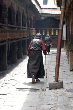 Tibetan woman rotating the prayer wheels... always moving clockwise!