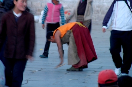 Picture 1 of 4: buddhist pilgrim postrating around the Jokhang's kora