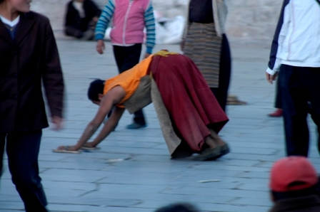 Picture 2 of 4: buddhist pilgrim postrating around the Jokhang's kora