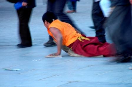 Picture 3 of 4: buddhist pilgrim postrating around the Jokhang's kora